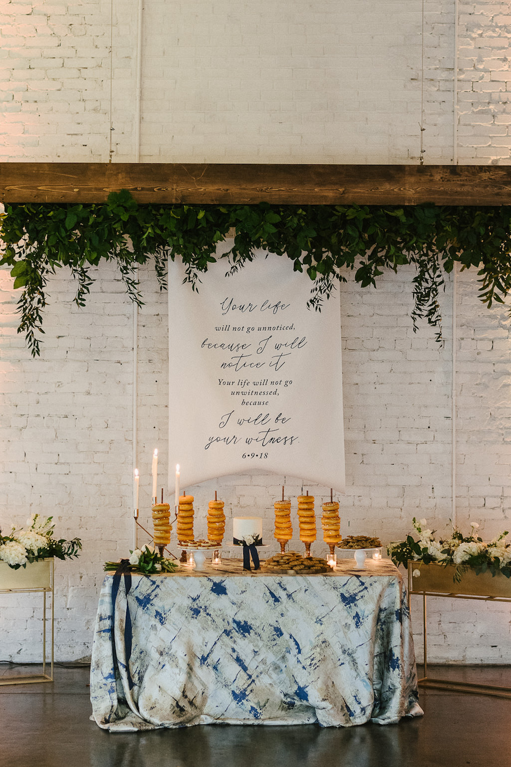 Rustic Wedding Reception Dessert Table with Cookies and Mini Doughnuts, Candlesticks, One Tier White Wedding Cake on Artsy Blue and White Linen, Upside Down Wooden Planterbox and Green Leaves and White Fabric Wedding Banner | Lakeland Wedding Venue Haus 820 | Tampa Bay Wedding Rentals Over the Top Linens