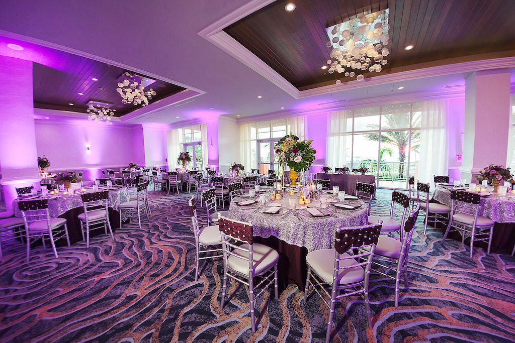 Elegant Ballroom Wedding Ceremony Reception Decor, Purple Uplighting, Round Tables with Silver and Dark Purple Tablecloths, Silver Chiavari Chairs with Plum Woven Chair Sash and Tall Gold Vase, Floral and Greenery Bouquet | Tampa Bay Rentals Over the Top Linens | Wedding Venue Hyatt Regency Clearwater Beach