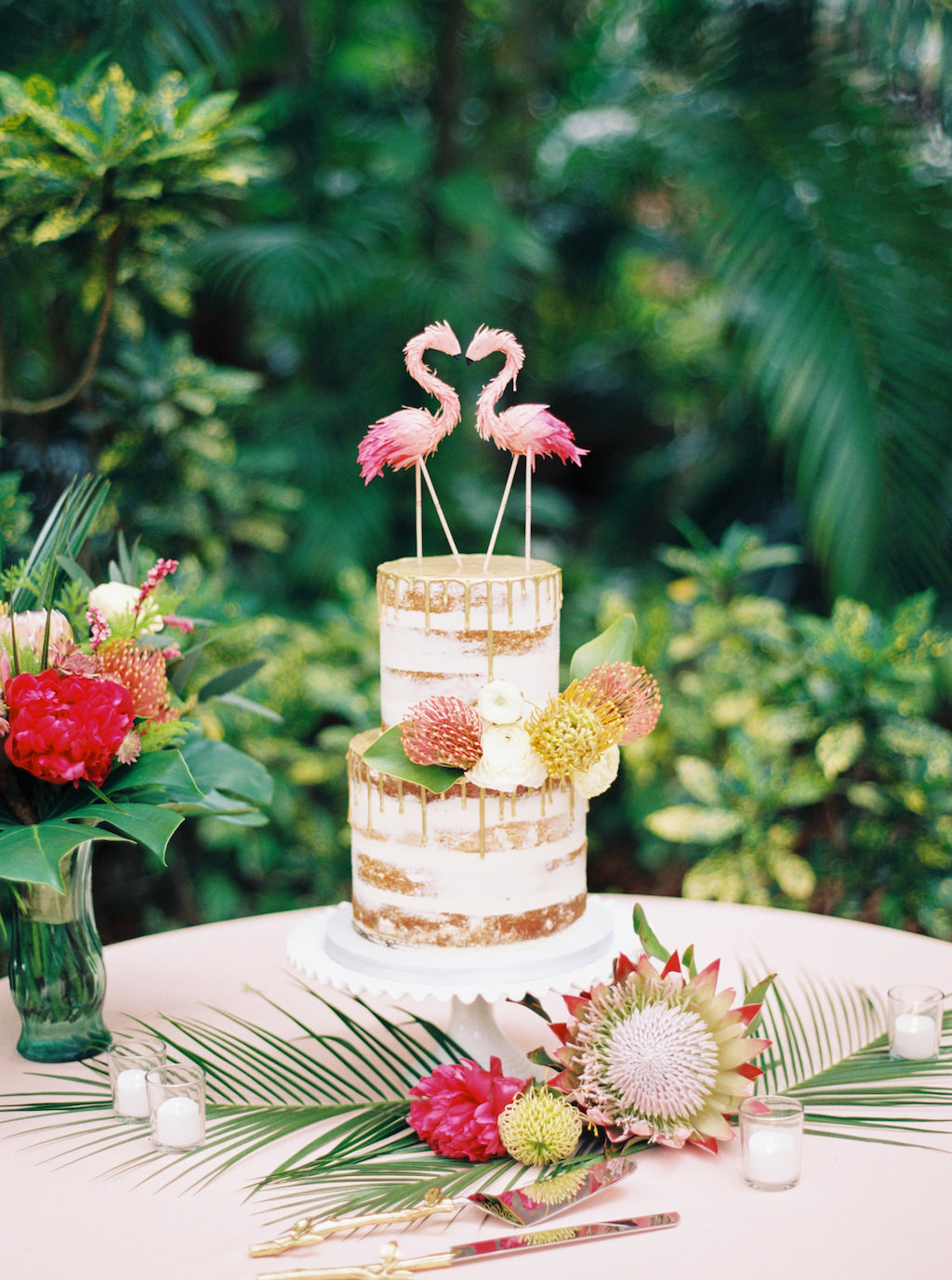 Round Two Tier Semi Naked Wedding Cake and Gold Drip Detailing with Fresh Tropical Flowers, Pink Flamingo Cake Topper