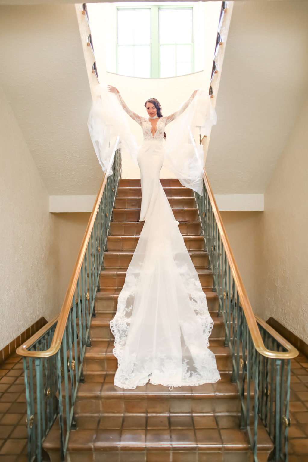 Bridal Portrait on Staircase, Lace and Sheer Long Sleeve Low V-Neck Wedding Dress with Long Train and Veil, Braided Hairstyle | St. Petersburg Photographer Lifelong Photography Studios