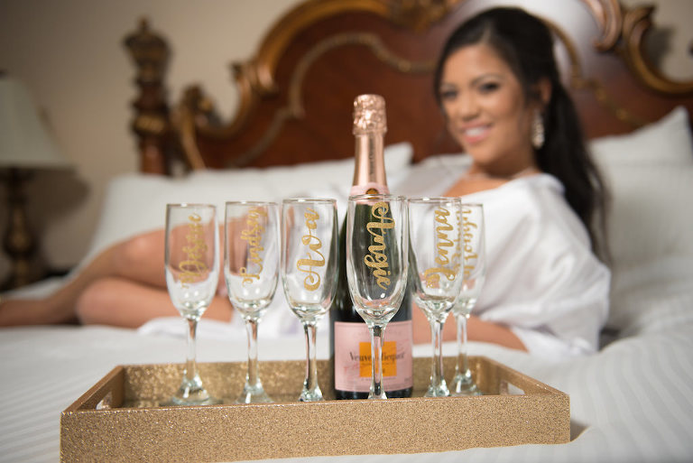 Creative Bride Getting Ready Portrait on Bed with Personalized Champagne Glasses on Gold Glitter Tray