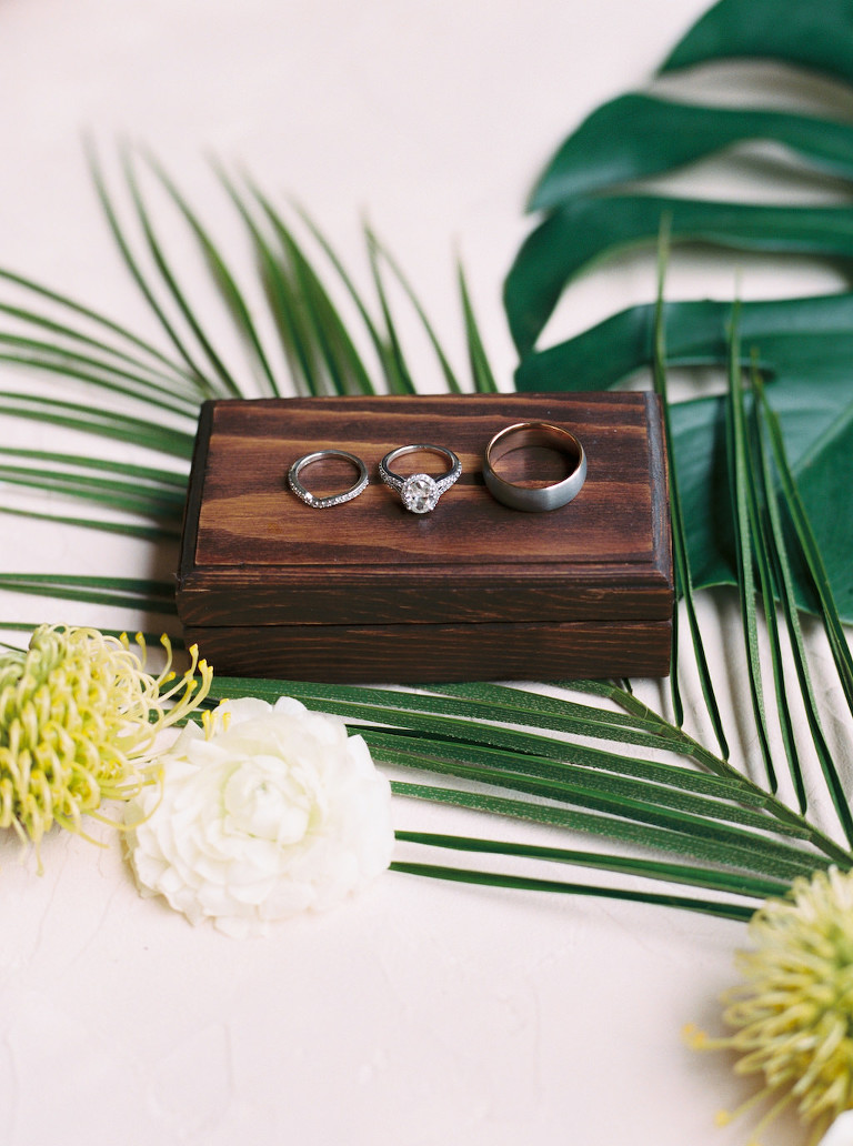 Wedding Rings on Wooden Box and Palm Tree Leaves