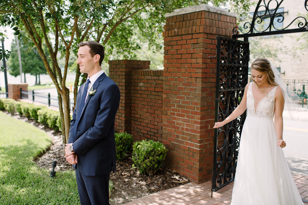 Outdoor Bride and Groom First Look Wedding Portrait, Groom in Navy Blue Suit and White Floral Boutonniere, Bride in White A-Line Illusion Tank Top Strap Plunging V-Neckline and Lace Bodice Wedding Dress