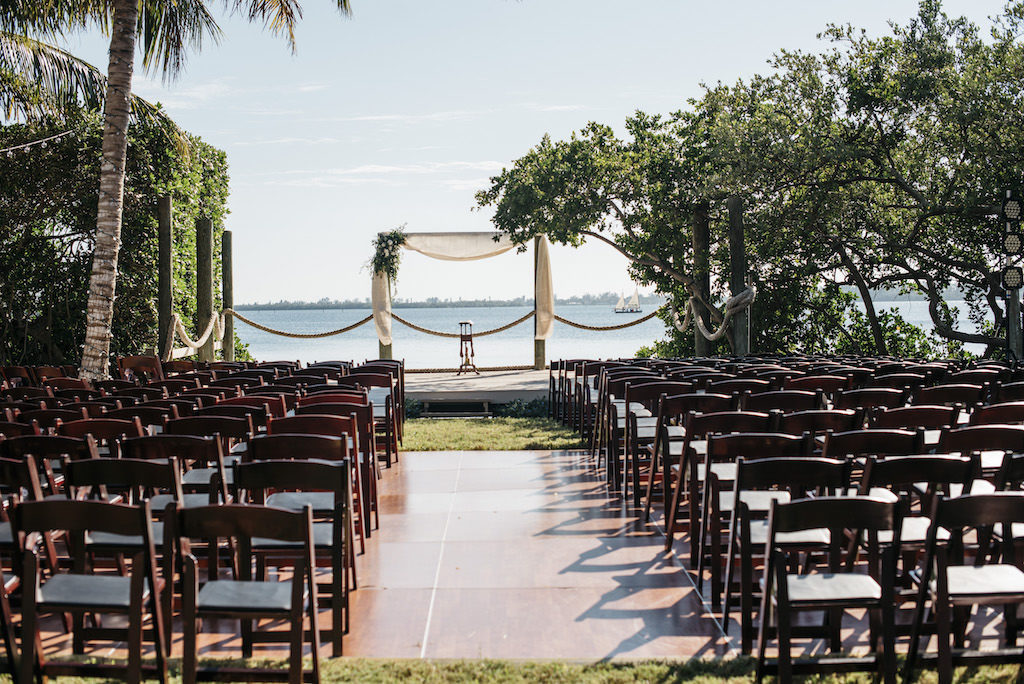 Waterfront Wedding Ceremony, Brown Wooden Folding Chairs, Arch with White Draping and Greenery and White Floral Bouquet | Sarasota Wedding Planner Kelly Kennedy Weddings and Events