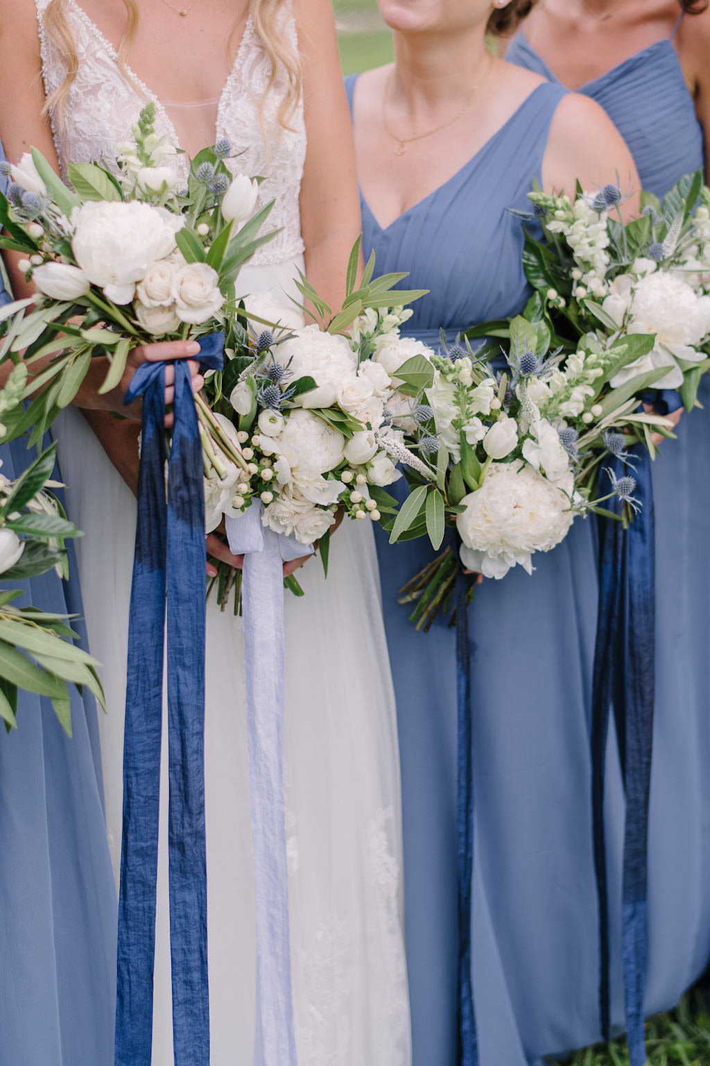 Outdoor Bridal Party Portrait, Bride in Plunging V Neck Illusion Lace A Line Wedding Dress, Bridesmaids in Dusty Blue Tank Top Dresses and White and Greenery Floral Bouquets