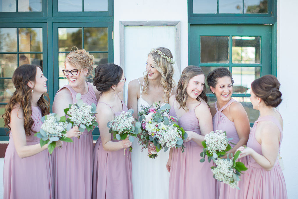 Bride and Bridesmaids Wedding Portrait, Bridesmaids in Dusty Rose Mismatched Dresses with Baby's Breathe Bouquets, Bride in A-line Spaghetti Strap Lace Wedding Dress with Hair Curled Down and Floral Crown Hairpiece | Tampa Bay Hair and Makeup Femme Akoi Beauty Studio