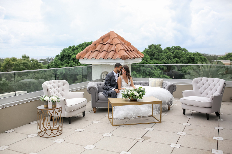 Bride and Groom Hotel Rooftop Wedding Portrait on Grey Modern Tufted Couch, Gold Coffee Table with White and Greenery Floral Centerpiece, White Tufted Armchairs, Gold Side Table with White Florals in Vases | Tampa Bay Photographer Lifelong Photography Studios | Planner Parties A'la Carte | Florist Cotton and Magnolia | Downtown St. Pete Wedding Venue The Birchwood | Rentals A Chair Affair
