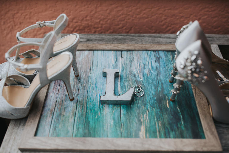 Silver Sparkle Strappy Sandal Strappy Stiletto Wedding Shoes and Silk Silver Pumps with Rhinestone Heel Wedding Shoes on Wooden and Teal Blue Sign with Letter L and Wedding Rings