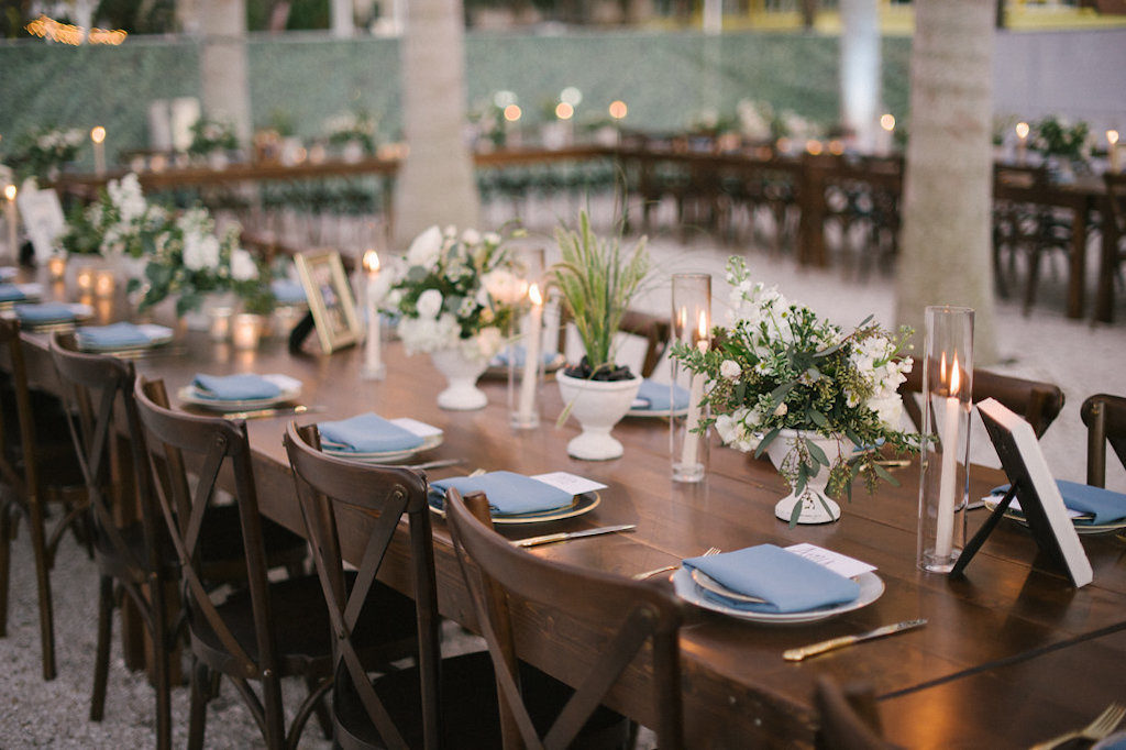 Long Wooden Feasting Table with Wood Crossback Chairs, Low White Vases with White and Greenery Floral Centerpieces, Tall Glass Vases with Candlesticks, Picture Frames, and Pale Blue Napkin Linens on Antique China Plates | Tampa Bay Rental Company A Chair Affair | Unique St. Petersburg Venue Intermezzo Coffee and Cocktails