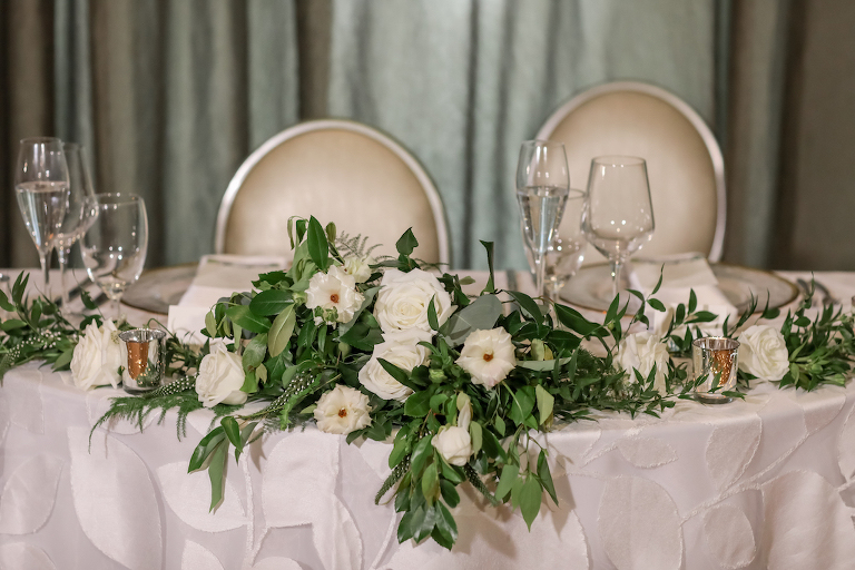 Elegant Ballroom Wedding Reception Decor, Sweetheart Table with White and Greenery Florals, Silver Votives and White Floral Tablecloth | Tampa Bay Photographer Lifelong Photography Studios | Rentals A Chair Affair and Over the Top Rental Linens | Florist Cotton and Magnolia | Planner Parties A'la Carte