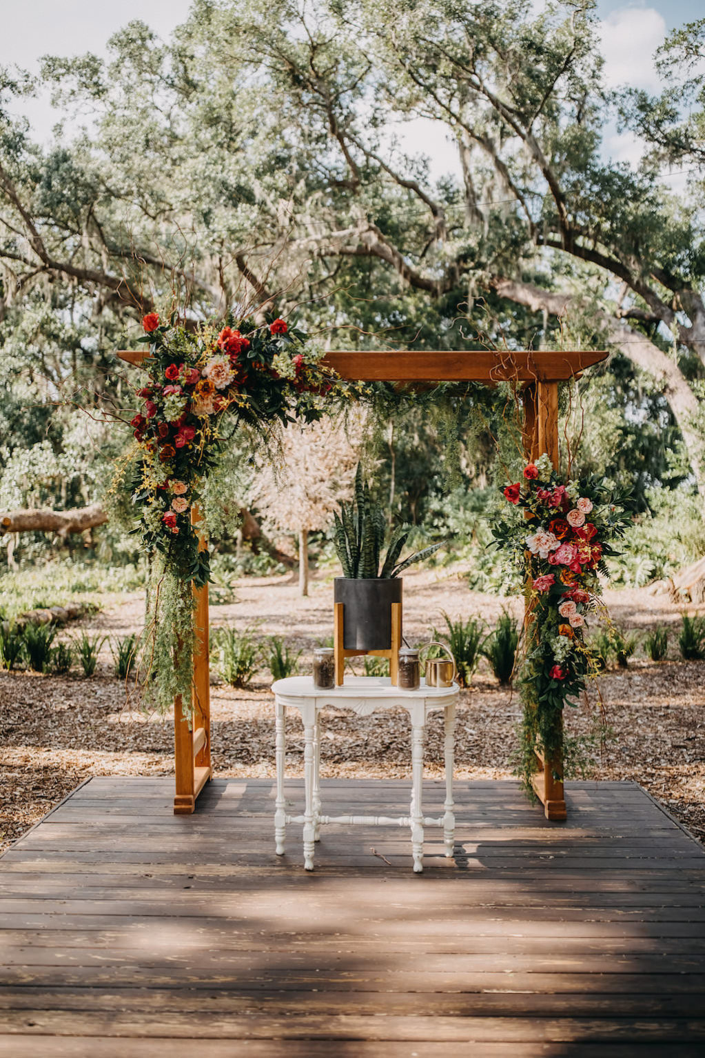 Outdoor Tropical Inspired Wedding Ceremony Decor, Wooden Arch with Pink, Yellow, Orange, Red and Greenery Bouquets, White Ceremony Table with Black and Gold Vase withe Palm Tree Leaves | Tampa Bay Photographer Rad Red Creative | Venue Cross Creek Ranch