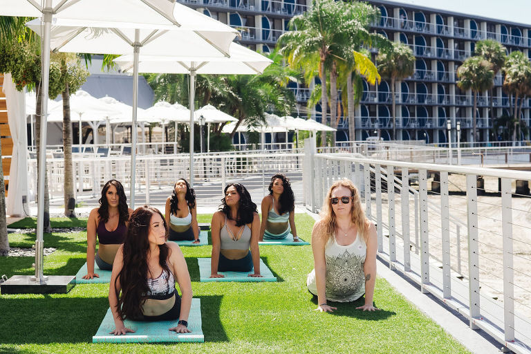 Tampa Bay Bachelorette Party Doing Yoga Outside on Lawn of Hotel by Beach | Tampa Bay Wedding Yoga Services Fifth Sign Yogi | Tampa Bay Wedding Venue The Godfrey Hotel | Hair and Makeup Michele Renee the Studio | Photographer Grind and Press Photography