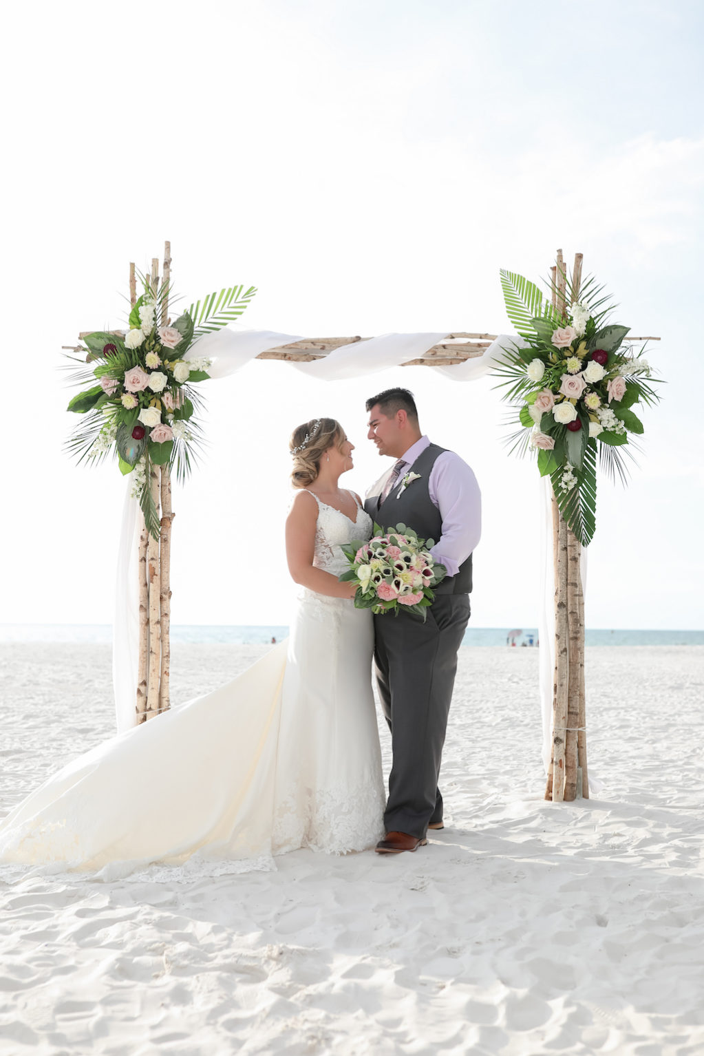 Clearwater Beach Waterfront Bride and Groom Wedding Ceremony Portrait Under Birchwood Arch with Blush pink, White and Red Florals with Green Palm Leaves | Tampa Bay Wedding Photographer Lifelong Photography Studios | Clearwater Beach Hotel Wedding Venue Hilton Clearwater Beach