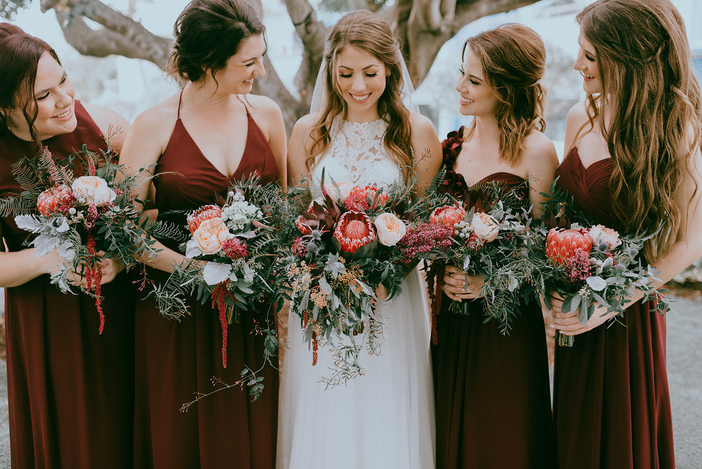 Bride and Bridesmaids Wedding Portrait, Bridesmaids in Long Burgundy Mismatched Style Dresses, Bride in High Neck Illusion and Lace Wedding Dress with, Red, Blush Pink, Greenery Organic Floral Bouquets | Tampa Bay Hair and Makeup Artist Michele Renee the Studio