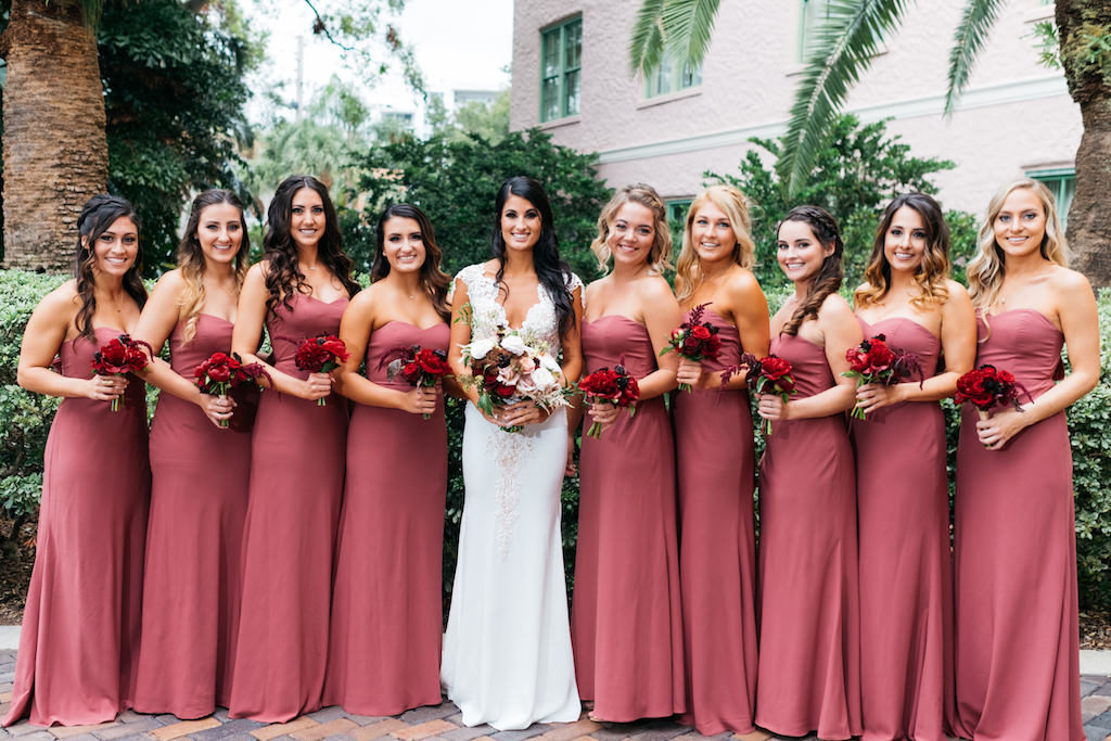 St. Petersburg Bride and Bridesmaid Outdoor Wedding Portrait, Bride in Romantic Fitted Lace and Illusion Deep V-Neck Pnina Tornai Wedding Dress and Garden Inspired Blush Pink, White, Red and Greenery Floral Bouquet, Bridesmaids in Matching Strapless Dusty Rose Dresses with Red Floral Bouquets | Tampa Bay Bridesmaids Dresses Bella Bridesmaids | St. Petersburg Wedding Planner Parties A'la Carte