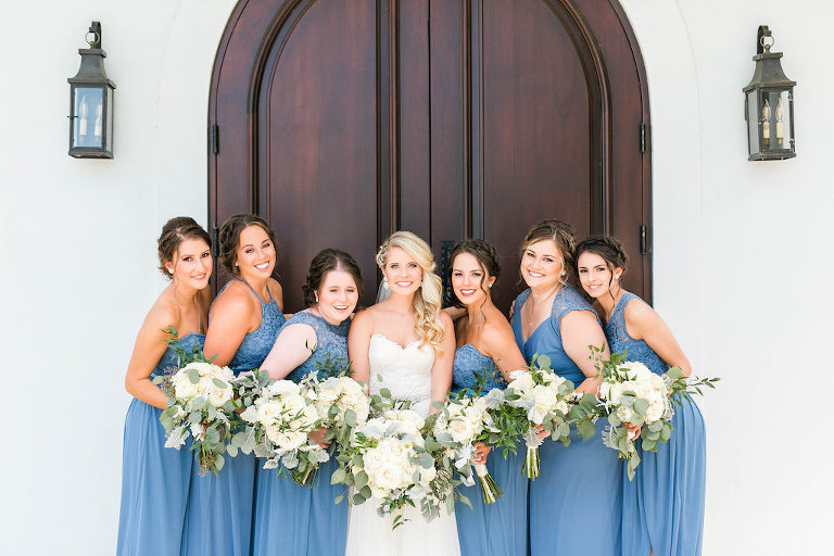 Bride and Bridesmaids Wedding Portrait, Bride in Sweetheart Strapless Lace A-Line Wedding Dress, Bridesmaids in Dusty Blue Mismatched Style Dresses with White/Ivory and Greenery Floral Bouquets | Tampa Bay Hair and Makeup Femme Akoi | Clearwater Wedding Ceremony Venue Harborside Chapel