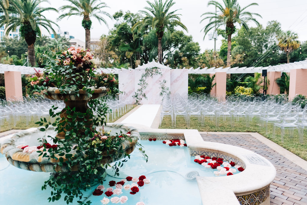 Elegant Outdoor Courtyard Wedding Ceremony Decor, Blush Pink, Dusty Rose, Red and Greenery Cascading Florals on Fountain, Red and Blush Pink Roses Floating in Fountain, Clear Acrylic Chairs | Tampa Bay Wedding Planner Parties A'la Carte | St. Petersburg Hotel Wedding Venue The Vinoy Renaissance
