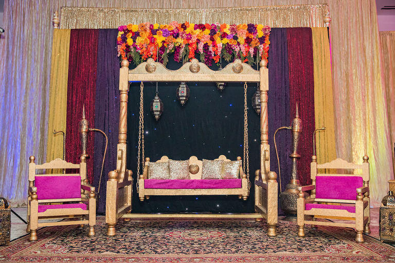 Glamorous Indian Wedding Reception Decor, Gold Swing with Purple and Gold Cushions with Colorful Pink, Purple, Orange, Yellow Flower Arch, Gold Chairs with Purple Cushions, Yellow, Dark Red, Purple and Gold Linen Backdrop | Tampa Bay Wedding Venue Wyndham Grand Clearwater Beach