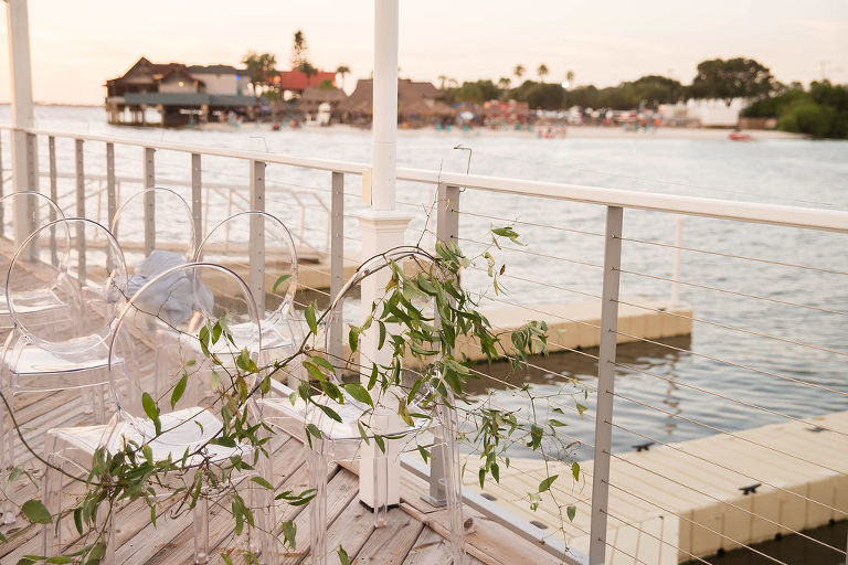 Florida Outdoor Waterfront Wedding Ceremony Decor, Clear Acrylic Chairs and Greenery Garland | Tampa Wedding Photographer Kristen Marie Photography | Tampa Wedding Venue The Godfrey | Rentals Gabro Event Services