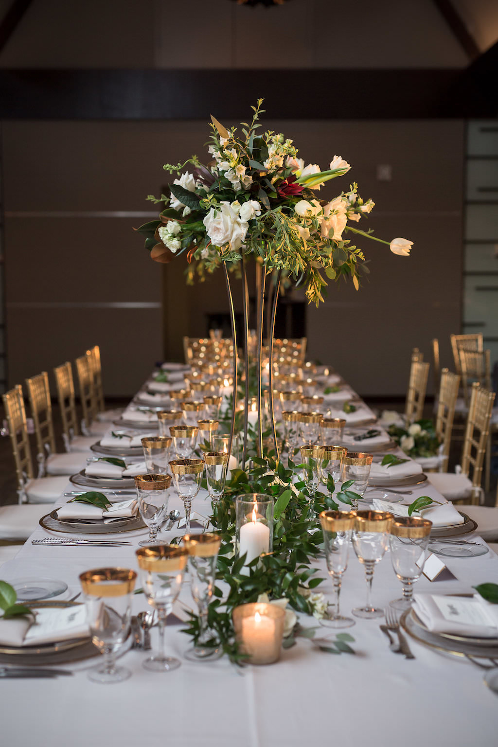 Modern, Elegant Wedding Reception Decor, Long Feasting Table with Tall Gold Stand with Organic Greenery and White Floral Centerpiece, Greenery Garland Table Runner, Candles and Gold Rimmer Glasses, Gold Chiavari Chairs | Tampa Bay Photographer Cat Pennenga Photography| Sarasota Wedding Planner NK Productions