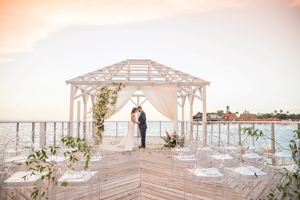 Florida Outdoor Waterfront Wedding Ceremony Bride and Groom Portrait Under Wooden White Canopy with Arch Draped with White Linen, Greenery Leaves and Ivory and Blush Pink Florals, Acrylic Chairs with Greenery Garland | Tampa Wedding Photographer Kristen Marie Photography | Tampa Venue The Godfrey | Draping and Ghost Chair Rentals Gabro Event Services Instagram