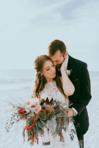 Beach Waterfront Bride and Groom Wedding Portrait with Wild Organic Red, Burgundy, Blush Pink and Greenery Floral Bouquet, Bride in Lace and Illusion High Neck Wedding Dress | St. Petersburg Wedding Venue Postcard Inn on the Beach | Tampa Bay Hair and Makeup Artist Michele Renee the Studio