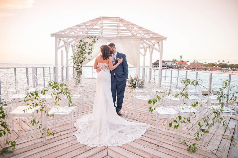 Florida Outdoor Waterfront Wedding Ceremony Bride and Groom Portrait Under Wooden White Canopy with Arch Draped with White Linen, Greenery Leaves and Ivory and Blush Pink Florals, Acrylic Chairs with Greenery Garland | Tampa Wedding Photographer Kristen Marie Photography | Tampa Venue The Godfrey | Draping and Ghost Chair Rentals Gabro Event Services