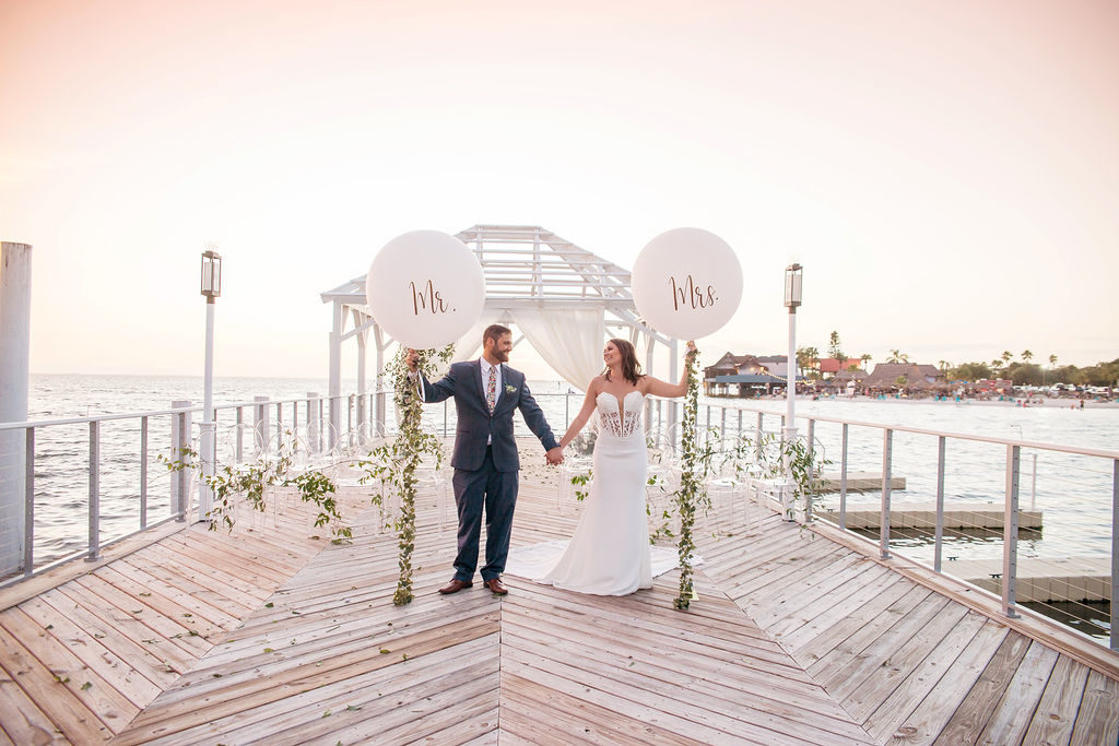 Florida Outdoor Waterfront Bride and Groom Wedding Ceremony Portrait, Bride and Groom Holding Custom White Mr. and Mrs. Large Oversized White Balloons with Garland String | Tampa Wedding Photographer Kristen Marie Photography | Tampa Venue The Godfrey Instagram