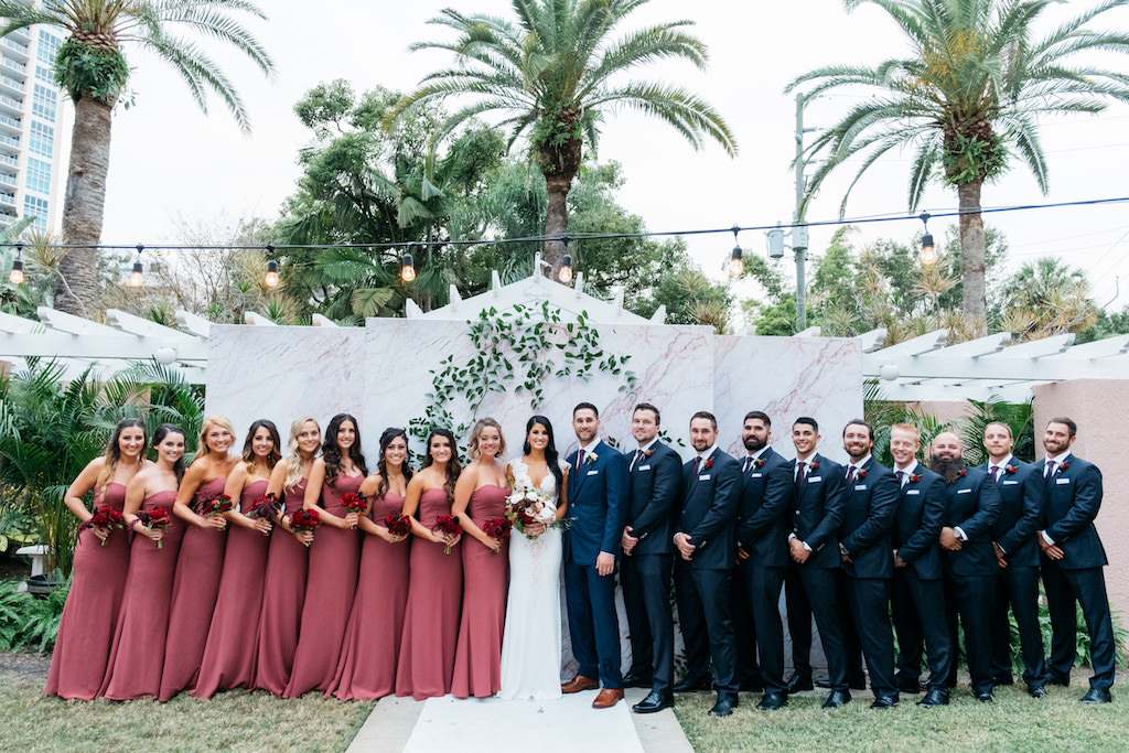 Elegant Outdoor Bride Groom And Bridal Party Wedding Portrait Bridesmaids In Dusty Rose Dresses With Red Floral Bouquets Groomsmen In Navy Blue Suits Bride In Fitted Lace And Illusion Cap Sleeve Deep