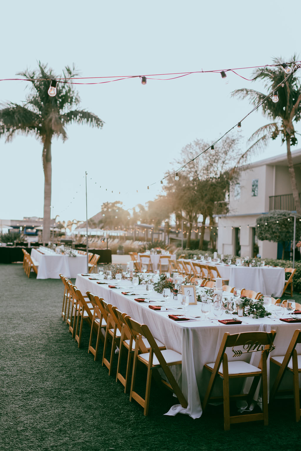 Outdoor Garden Lawn Wedding Reception Decor Long Feasting Table White Tablecloths Burgundy Linens Wooden Folding Chairs With White Cushions Low Floral Centerpieces St Petersburg Wedding Venue Postcard Inn On The Beach