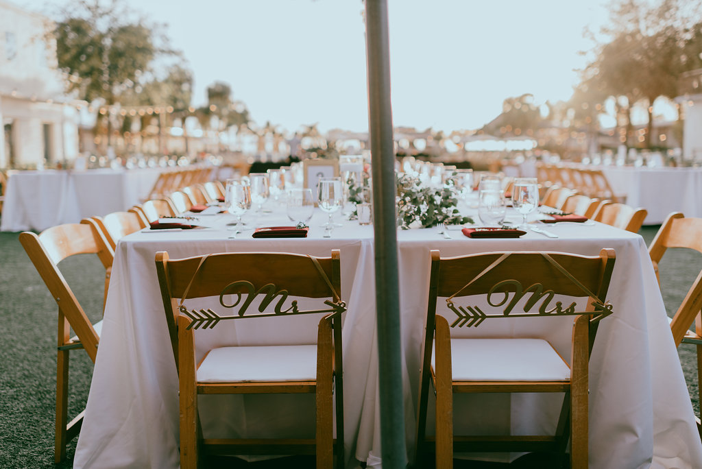 Outdoor Garden Lawn Wedding Reception Decor Long Feasting Sweetheart Table White Tablecloth Wooden Folding Chairs With White Cushions And Custom Lasercut Chair Signs Marry Me Tampa Bay Local Real Wedding