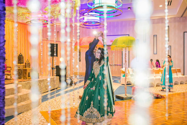 Glamorous Indian Wedding, Bride in Traditional Green and Gold Sari Dancing with Groom in Hotel Ballroom and Hanging Crystals | Tampa Bay Wedding Venue Wyndham Grand Clearwater Beach