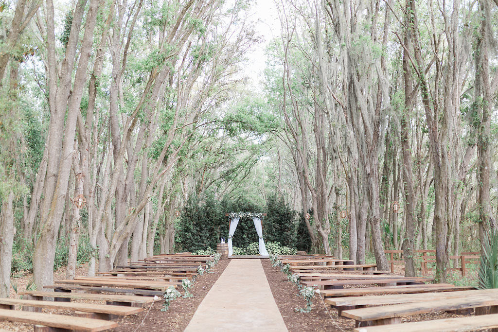 Rustic Elegant Wedding Tampa Bay Ceremony Outdoors, Wooden Benches, Wooden Arch with White Linen Draping and Greenery | Plant City Wedding Venue Florida Rustic Barn Weddings