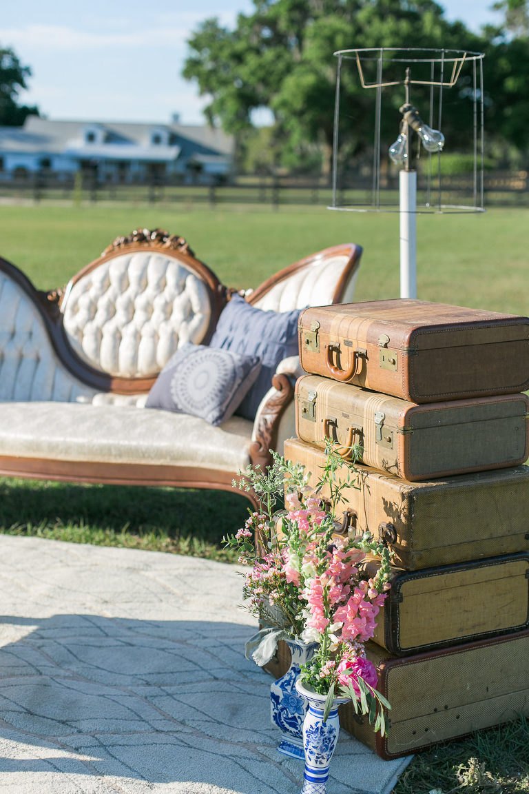 Vintage Outdoor Tampa Wedding Ceremony Decor, Old Suitcases Stacked, Antique Vase with Pink Florals, Vintage Ivory Couch