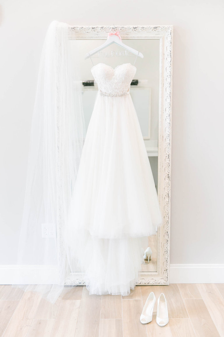 Sweetheart Strapless A-Line Lace Bodice Wedding Dress with Rhinestone Belt Hanging on Mirror