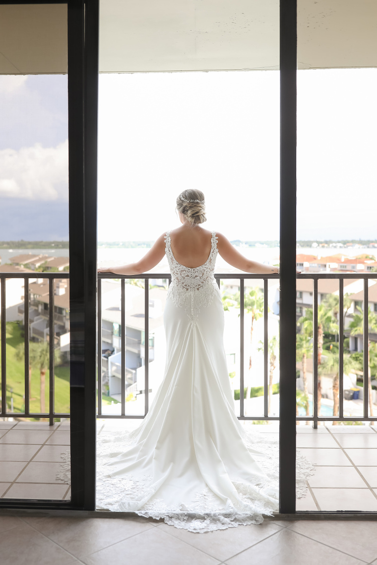 Florida Bride on Balcony of Hotel in Scoop Back Lace Fitted Wedding Dress | Tampa Bay Wedding Photographer Lifelong Photography Studios | Clearwater Beach Hotel Wedding Venue Hilton Clearwater Beach