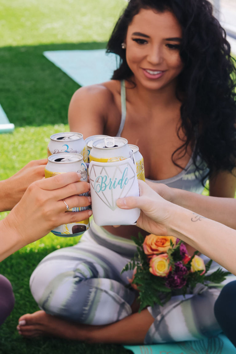 Tampa Bay Bachelorette Party Doing Yoga on Lawn of Hotel Cheering with Custom Koozies   Tampa Bay Wedding Yoga Services Fifth Sign Yogi   Tampa Bay Wedding Venue The Godfrey Hotel   Hair and Makeup Michele Renee the Studio   Photographer Grind and Press Photography