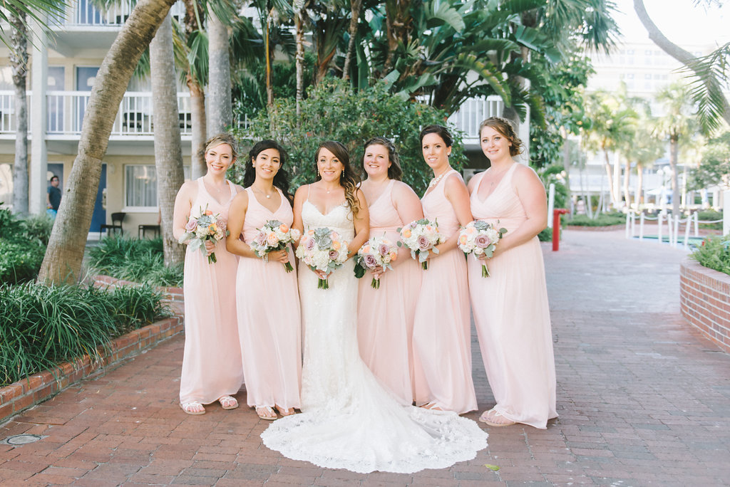 Outdoor Florida Bride and Bridesmaids Wedding Portrait in V Neck Lace Fitted and Spaghetti Strap Wedding Dress with White Hydrangeas, Blush Pink and Succulent Floral Bouquet, Bridesmaids in Matching Long Blush Pink Dresses | Tampa Bay Photographer Kera Photography | Hair and Makeup Michele Renee the Studio