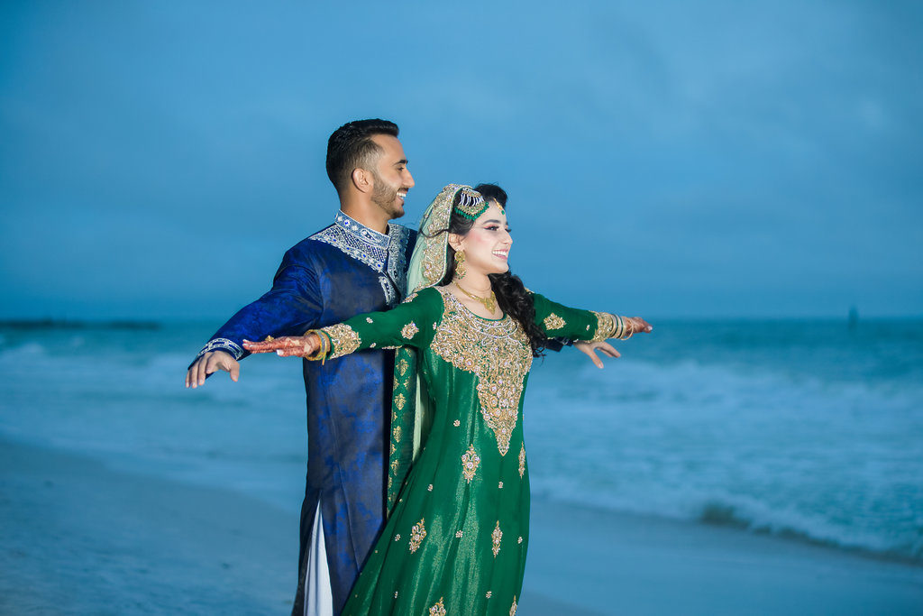 Indian Bride and Groom on Beach Wedding Portrait, Bride in Traditional Green and Gold Sari with Henna Tattoo, Groom in Traditional Blue and White Attire   Tampa Bay Wedding Venue Wyndham Grand Clearwater Beach