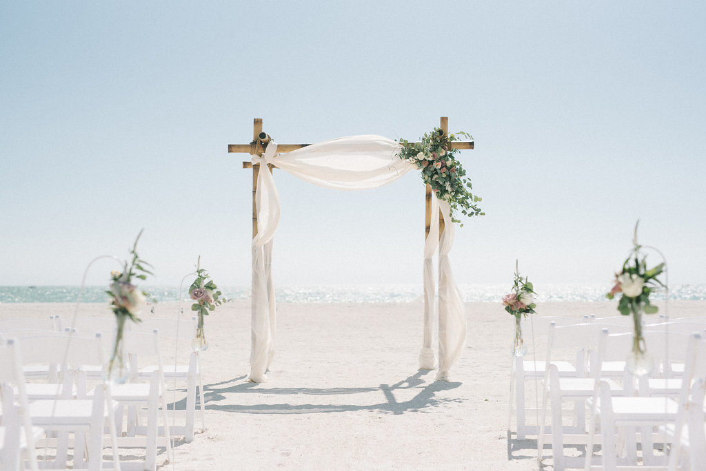 Outdoor Beach Wedding Ceremony Decor, Wooden Arch with White Linen Drapery, Greenery, White and Blush Pink Florals, White Wooden Folding Chairs, Floral Bouquets on Stands | Tampa Bay Photographer Kera Photography | St. Pete Beach Wedding Venue Tradewinds Island Resort