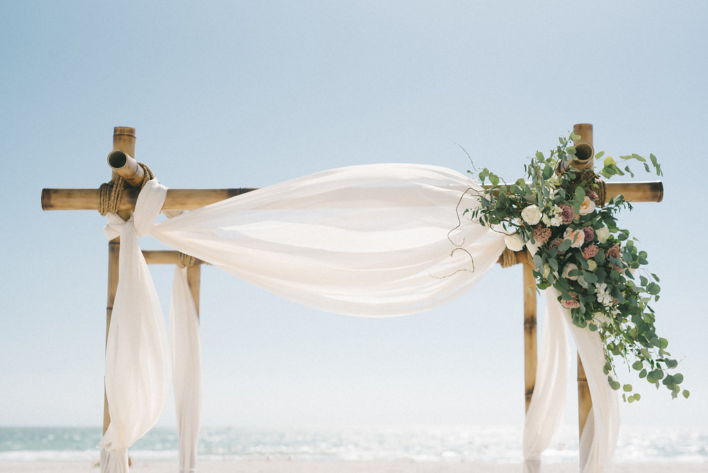 Outdoor Beach Wedding Ceremony Decor, Wooden Arch with White Linen Drapery, Greenery, White, Lilac and Blush Pink Florals | Tampa Bay Photographer Kera Photography | Rentals A Chair Affair