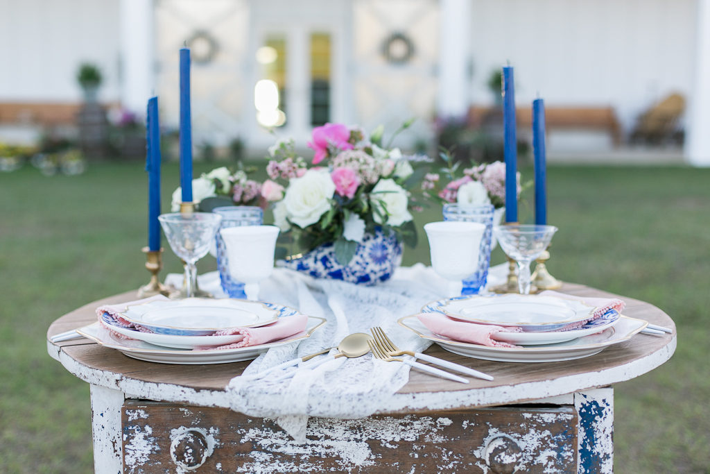 Vintage Inspired Wedding Reception Decor, Tall Antique Cocktail Table, White Lace Table Runner, Blue Candlesticks, Blue and White Vase with White and Pink Florals, Antique China with Blush Pink Linens