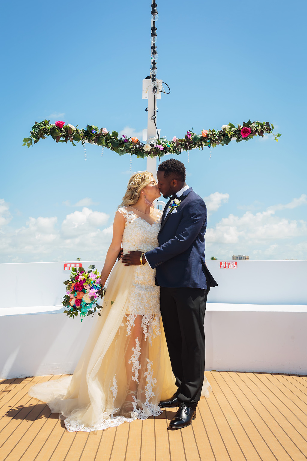Florida Bride and Groom Wedding Portrait on Deck of Yacht, Bride in Lace and Illusion with Tulle Train High Scoop Neckline Wedding Dress with Colorful Floral Bridal Bouquet, Groom in Navy Blue Tuxedo | Unique Waterfront Tampa Wedding Venue The Yacht Starship IV