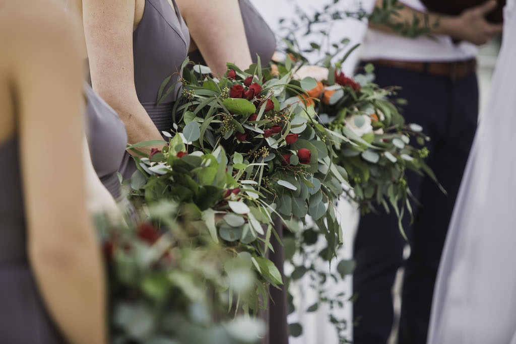 Outdoor Florida Beach Wedding Ceremony Portrait, Bridesmaids Holding Greenery and Red Floral Bouquets