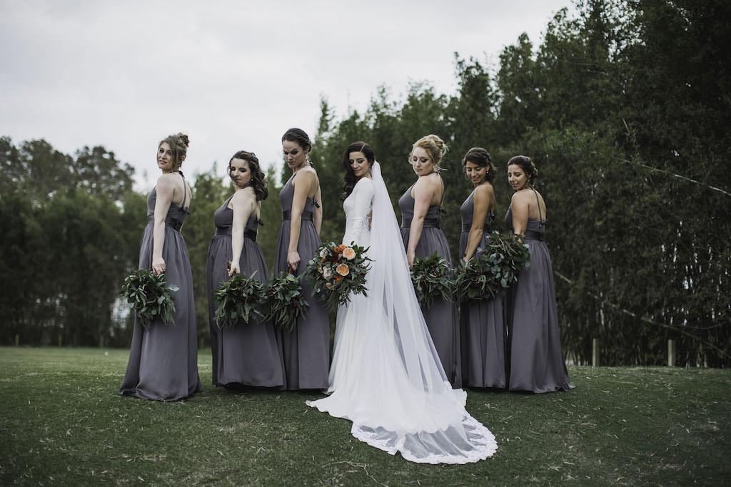 Outdoor Florida Bride and Bridesmaids Wedding Portrait, Bride in Crepe and Lace Mermaid Long Sleeve Wedding Dress with Cathedral Veil, Bridesmaids in Matching Halter Top Grey Long Dresses | Waterfront Venue Isla Del Sol Yacht and Country Club