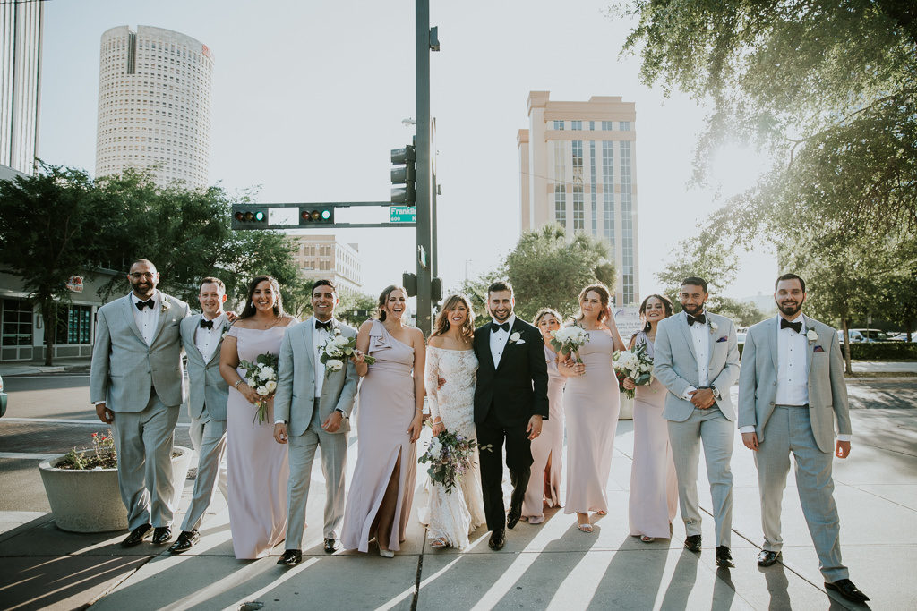 Outdoor Downtown Tampa Bride, Groom and Bridal Party Wedding Portrait, Bridesmaids in Lavender Dresses, Groomsmen in Grey Tuxedos, Bride in Lace and Illusion Scoop Neckline Long Sleeve Wedding Dress, Groom in Black Tuxedo | Tampa Bay Wedding Photographer Brandi Image Photography