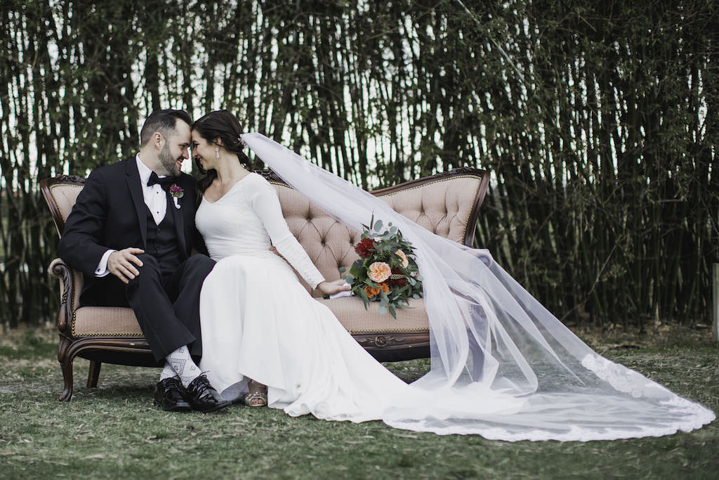 Outdoor Florida Bride and Groom Wedding Portrait on Blush Pink Vintage Loveseat Couch, Bride in Crepe and Lace Long Sleeve V Neckline Mermaid Wedding Dress with Cathedral Veil, Groom in Black Tuxedo