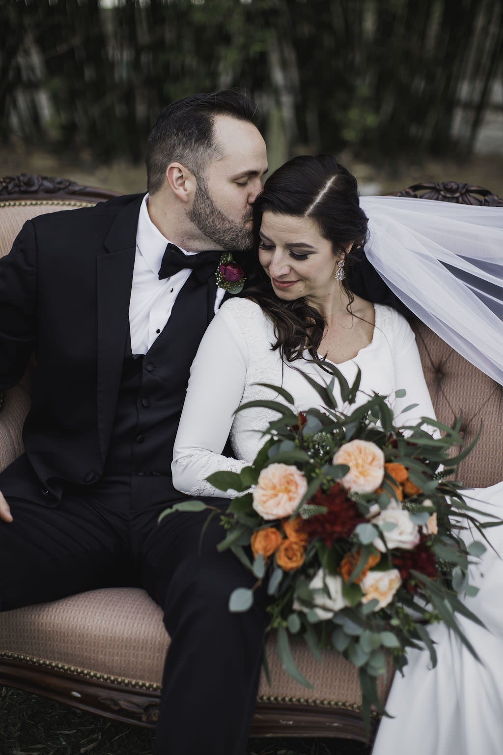 Outdoor Florida Bride and Groom Wedding Portrait on Blush Pink Vintage Loveseat Couch, Bride in Crepe and Lace Long Sleeve V Neckline Mermaid Wedding Dress with Cathedral Veil with Greenery, Blush Pink, Orange, and Red Floral Bouquet, Groom in Black Tuxedo