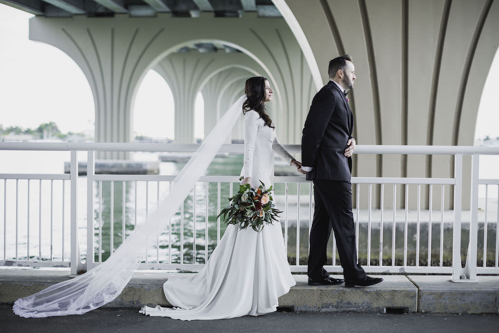 Outdoor St. Petersburg Florida Bride and Groom Wedding Portrait Under Intracoastal Waterway Bridge, Bride in Mermaid Crepe and Lace Long Sleeve Wedding Dress and Cathedral Veil with Greenery, Red, Blush Pink Floral Bouquet, Groom in Black Tuxedo