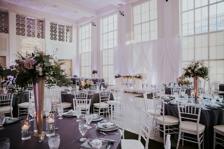 Modern Wedding Reception Decor with Silver Chiavari Chairs and Round Tables with Purple Linens, Tall Gold Vases and Blush Pink, Greenery, and White Floral Centerpiece | Downtown Tampa Wedding Venue The Vault | Tampa Bay Wedding Photographer Brandi Image Photography